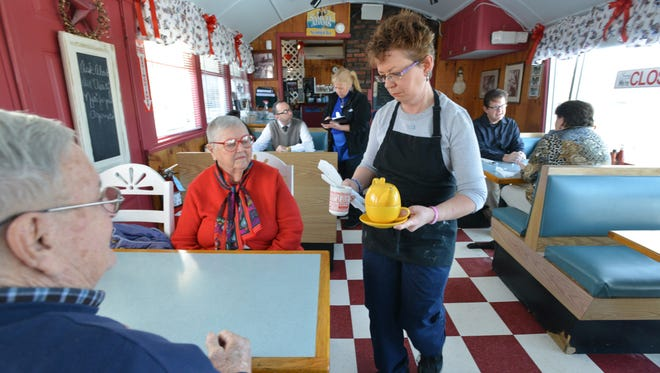 Sheila Bonfiglio, who owns the Three Dogz Diner with her husband George Bonfiglio, serves regulars Arthur and Carol St. Louis of Methuen, Mass.. The Bonfiglio's say that if state minimum goes up, they'll have to lay off workers or cut hours.