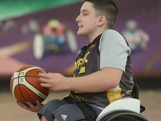 In the first game of the day Jeremy takes the ball down court and heads for the basket. The rules state that a player has to dribble only after they push the wheels of their wheelchair.
