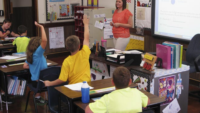 In this Sept. 18, 2013 photo, Shelly Ellis teaches fourth-grade students in a newly air conditioned classroom at Bement Elementary School in Bement, Ill. The results of the latest Nation's Report Card are in and the news isn't good. Fourth-graders made no improvements in math or reading, while eighth-graders' scores were flat in math and only slightly improved in reading.