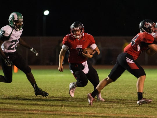 James M. Bennett quarterback Joey Blake (7) runs the