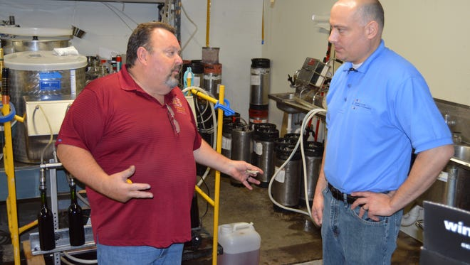 Lil' Ole Winemaker Shoppe owner Brian Larson, left, explains the business to Wausau Region Chamber of Commerce President/CEO Aaron Kapellusch.