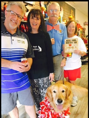 Lizzie, rescued by Golden Retriever Rescue of Mid-Florida, enjoys the company of friends at Tails at the Barkery. From left is Paul Hill, co-owner of the Dirty Oar Beer Company; Pam Shaia, owner of Tails at the Barkery: and Jerry and Judy Sheehan, GRRMF volunteers.