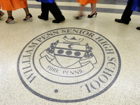 William Penn seniors pass by the school seal in the College Avenue lobby floor on their way to the commencement ceremony on Friday, June 6, 2014, at William Penn Senior High School.