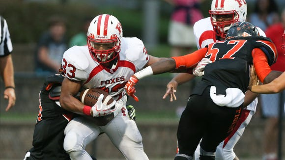 Fox Lane running back Andrew Brown, 33, breaks a tackle