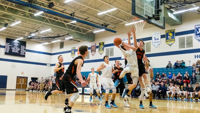 Armada High School's Dylan Szafranski (20) attempts to block Richmond's Chase Churchill during the MHSAA District basketball game at Richmond High School March 5.