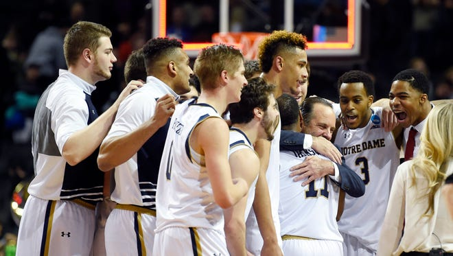 Notre Dame Fighting Irish head coach Mike Brey embraces his players.