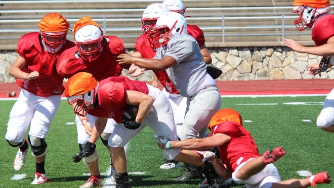 Several Glen Rose Tigers converge to tackle a teammate carrying the ball during preseason football practice at Tiger Stadium.