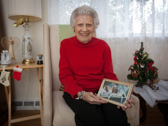 Jane Ashbaugh sits with a photo of one of her first foster children, Airie. Despite her age, 96-year-old Ashbaugh continues to give. Ashbaugh became a foster mother at the age of 76, and saw 17 children pass through her house. Now, she continues to give by ringing the bells for the Salvation Army.
