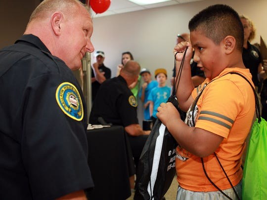 First grader Zaid Martinex (6) gets a backpack from Gallatin Chief of Police Don Bandy helps hand out school supplies at the Health Expo at West Eastland Church of Christ in Gallatin on Saturday, Aug. 5.