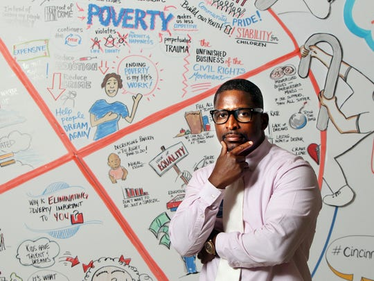 Torrance Jones, workforce developer at the Urban League of Greater Cincinnati, stands in front of a poster created during a recent Child Poverty Collaborative community summit held at Xavier University.
