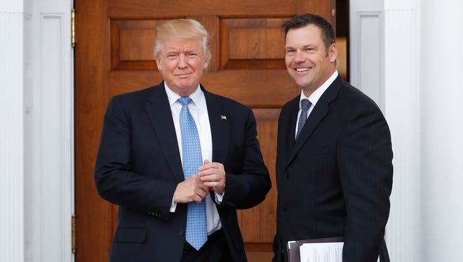 Kansas Secretary of State Kris Kobach, right, holds a stack of papers as he meets with then President-elect Trump on Nov. 20, 2016 at the Trump National Golf Club Bedminster clubhouse in Bedminster, N.J.