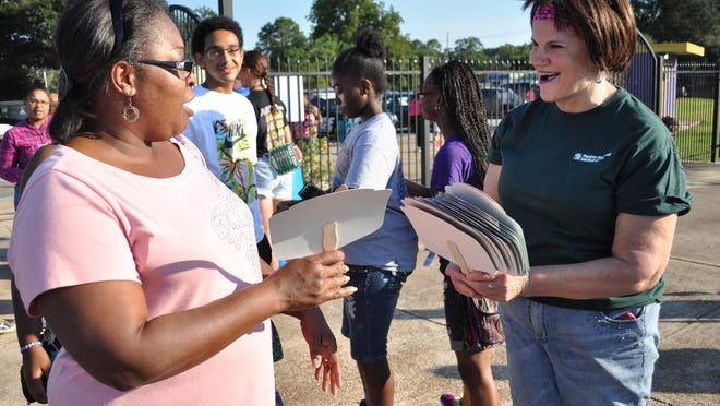 Liz Chevalier, a R.N. at Rapides Regional Medical Center, hands out fans Friday during the football jamboree at Alexandria Senior High School.