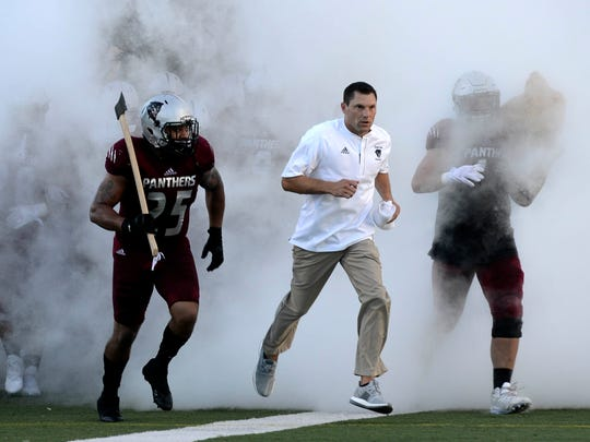 Florida Tech head football coach Steve Englehart leads his team onto the field.