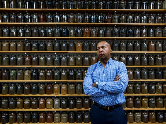 """Bryan Stevenson, Executive Director of the Equal Justice Initiative, is shown standing before jars containing soil from the sites of confirmed lynchings in the state of Alabama. """"We have to change the historical landscape, to address this distortion in history where we have erected monuments to the Confederacy and have not acknowledged slavery,"""" he said."""