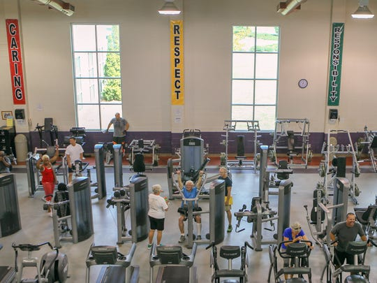 Members use exercise equipment at the Anderson Area YMCA. Outside the windows of the treadmills, a lawn can be seen where an expansion to the building will be built.