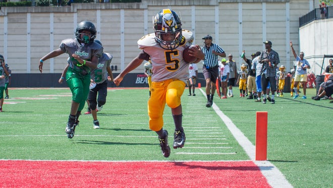 I'zaya Johnson, 9, jumps across the goal line for a touchdown in the second half of the game. More than 40 teams of kids gathered at the Sheakley Athletics Center for the 10th annual Peace Bowl Sunday July 31, 2016.