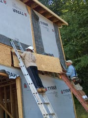From right, Mountain Housing Opportunities'  construction supervisor Joe Quinlan works with a volunteer to put sheathing on a house in Swannanoa. The nonprofit developer's Self-Help Homeownership Program allows low-income families to build their own neighborhoods in exchange for competitive mortgages and low-interest rates.