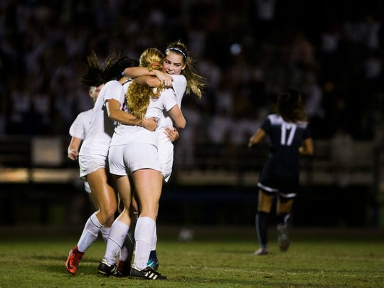 Estero's Maggie Struble hugs her teammates after scoring a goal to take the lead during the Class 4A state semifinal against Archbishop McCarthy High School on February 16, 2018, at Estero High School. The two schools face off again Friday for a spot in the state final.