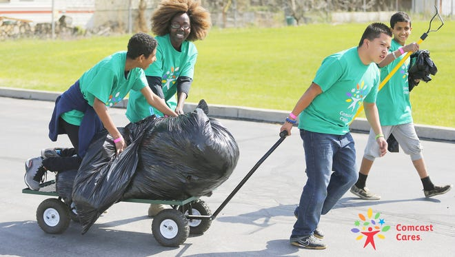 Volunteers have some fun as they pitch in to improve the school grounds and interior during Comcast Cares Day at Lincoln Elementary School in Salt Lake City  Saturday May 25, 2015.