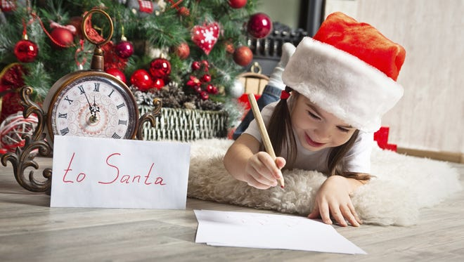 A girl in a Christmas hat writes a letter to Santa.