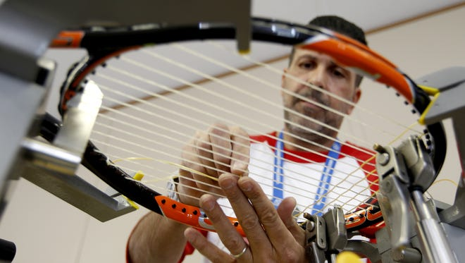 Enrique Reyes, a stringer with Priority One, strings a tennis racquet for one of the players at the Western and Southern Open.