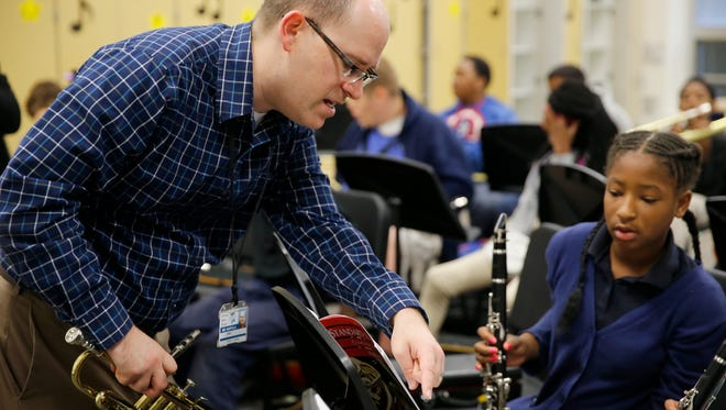 Brian Huhtala helps Yamaya Lee during band class at Chase Elementary School Thursday September 29, 2016. Cincinnati Public Schools is part of a big levy request this election.