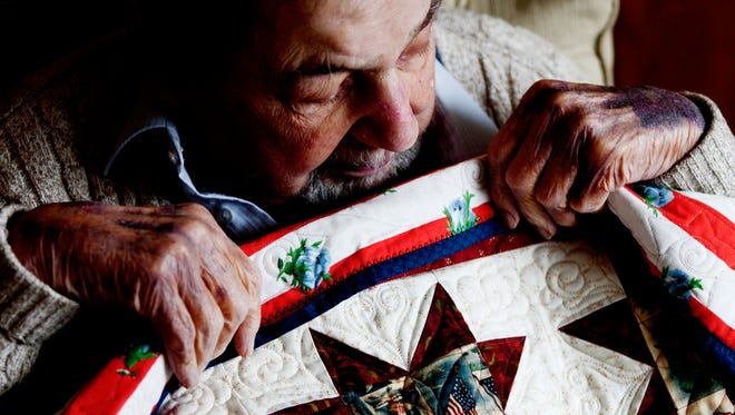 Charles Swain, 90, a World War II and Korean War veteran, is shown with his new quilt, given to him by Quilts of Valor at his home in Greenfield on Thursday. Quilts of Valor is a national organization that donates handmade quilts to combat veterans.