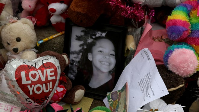 A photo of Alexandrea Thompson, 9, along with other items were left outside her Burnet Avenue home where she was shot and killed January 18, 2017.