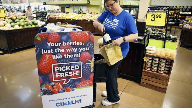 Tanya Barrett-Peters fills ClickList orders at the Kroger Marketplace in Oakley Friday, June 30, 2017. ClickList is Kroger's order online, pickup at the store service, that is being rolled out at supermarkets nationwide. This continues after Amazon announced it would takeover Whole Foods, leading analysts to believe digital grocery competition will heat up.