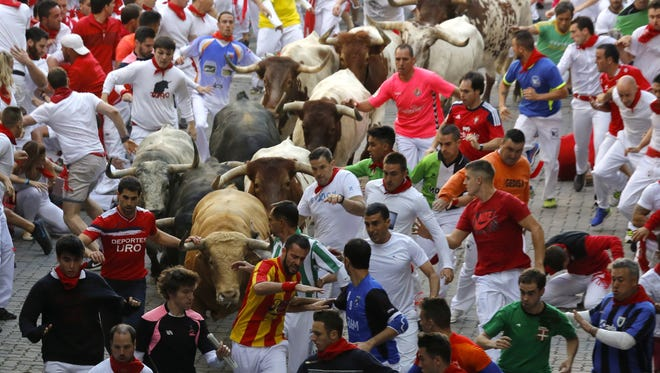Revellers run with Cebada Gago's fighting bulls entering the bullring during the second day of the San Fermin Running of the Bulls festival on July 7, 2017 in Pamplona, Spain.