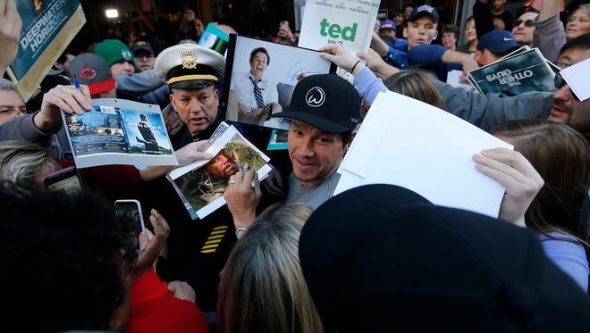Mark Wahlberg is surrounded by fans as he arrives for a private red-carpet event in February at his family's new restaurant Wahlburgers in Cincinnati.