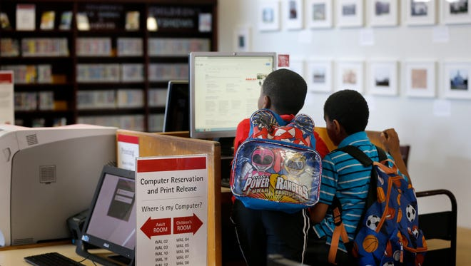 Children use a computer after school at the Walnut Hills branch library Friday April 13, 2018 . The Public Library of Cincinnati and Hamilton County seek a property tax increase that would double the current library property tax. The $19 million it would generate annually would go to renovating its old branches. The Walnut Hills is the oldest branch in the system that has never been renovated. It was built in 1906 and isn't ADA accessible.