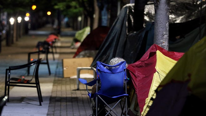 A homeless woman sits in front of her tent on Third Street, July 26, 2018.