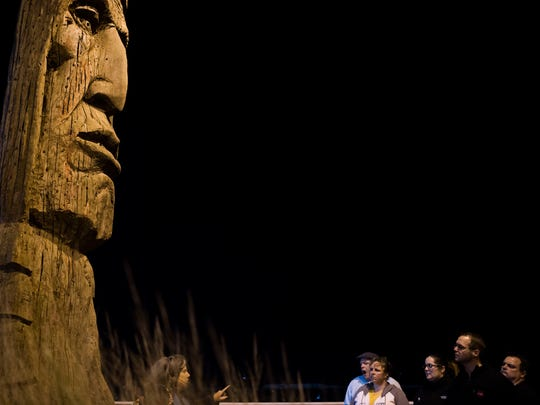 """Chesapeake Ghost Walks tour guide Mindie Burgoyne tells guests about Peter Toth's """"Whispering Giant"""" wooden statue near the Ocean City Life-Saving Station. They say one cannot stare into the eyes of the statue for more than 15 minutes without beginning to cry."""