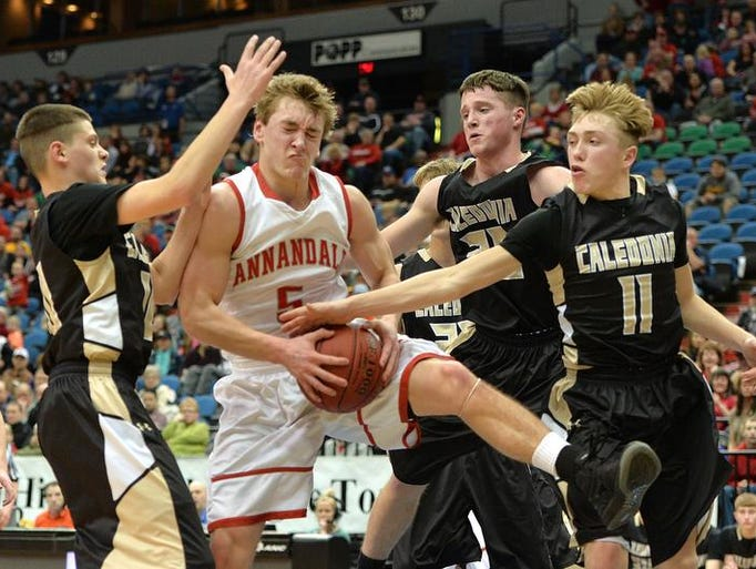 Annandale's Matt Miller (5) grabs a rebound against Caledonia defense during the first half of the Class 2A semifinal game of the boys' state basketball tournament Friday night at the Target Center in Minneapolis. The Cardinals led Caledonia 43-30 at half time.