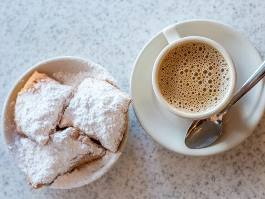 Beignets (French style donuts) topped with sugar and a cup of coffee in the background