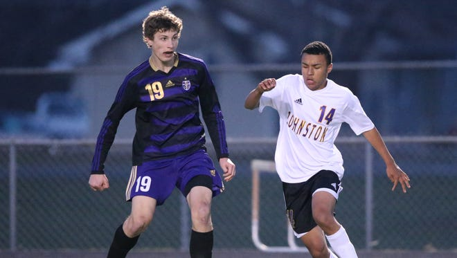 Johnston's Theo Nsereko, right, gives chase as Norwalk's Jacob Connelly (19) handles the ball during a boys' soccer match between Johnston and Norwalk on Thursday, April 17, 2014, at Johnston High School in Johnston, Iowa.