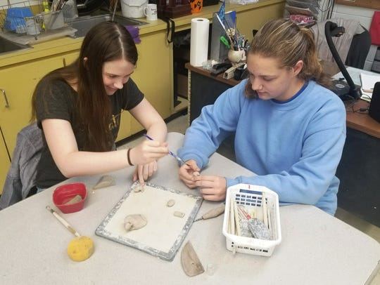 Students sculpt beads from clay and and add their own