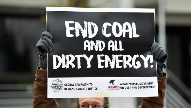 A protestor holds a sign demanding to end coal burning during the 23rd Conference of the Parties climate talks in Bonn, Germany, on Wednesday, Nov. 15, 2017.