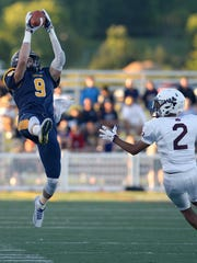 Victor's Andrew Russell, left, makes a catch while defended by Aquinas' Trent Collins.