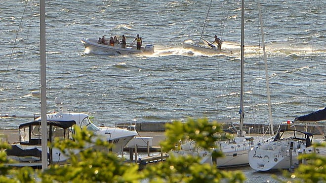 Boats head west on Presque Isle Bay under windy and choppy conditions in Erie. U.S. Coast Guard and Erie Bureau of Fire personnel responded to a call for six boats capsized in the water near the Erie Yacht Club, nearby, earlier Tuesday evening.