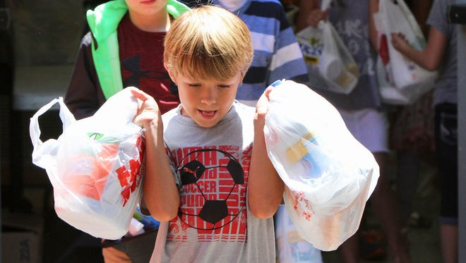 On Tueasday, Bayou View Elementary School second grader Ethan Borderon, 8, and other classmates load cleaning supplies at the Gulfport, Miss., school for flood victims in Louisiana. The city of Gulfport collected three truck loads of supplies and delivered them on Wednesday.