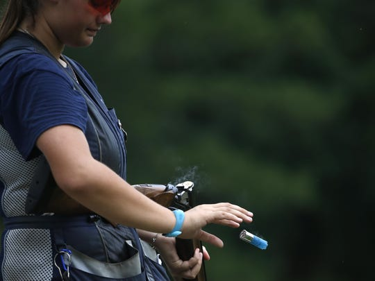 Abby Blakeley tosses an empty shell from her double-barreled shotgun after shooting at Bridge Creek Clays South Georgia Youth Shooting Club's clay pigeon range on Tuesday, June 30, 2015.
