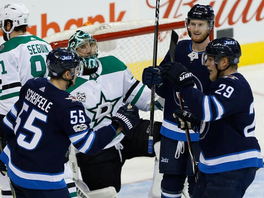 Winnipeg Jets' Mark Scheifele (55), Kyle Connor (81) and Patrik Laine (29) celebrate Scheifele's goal against Dallas Stars goaltender Ben Bishop during the first period of an NHL hockey game Thursday, Nov. 2, 2017, in Winnipeg, Manitoba. (John Woods/The Canadian Press via AP)