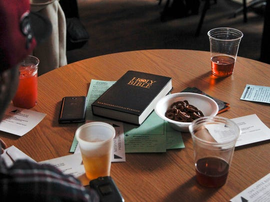 A Bible is seen on a table with beer and pretzels at The Loft in downtown Lansing, Michigan. More than 60 people gathered recently for the premiere of Crossroads Church's weekly gathering. This wasn't a church but a bar. Because they want people to come whose relationship with church is tenuous or non-existent, the pastors have promised to buy a drink for every first-timer.