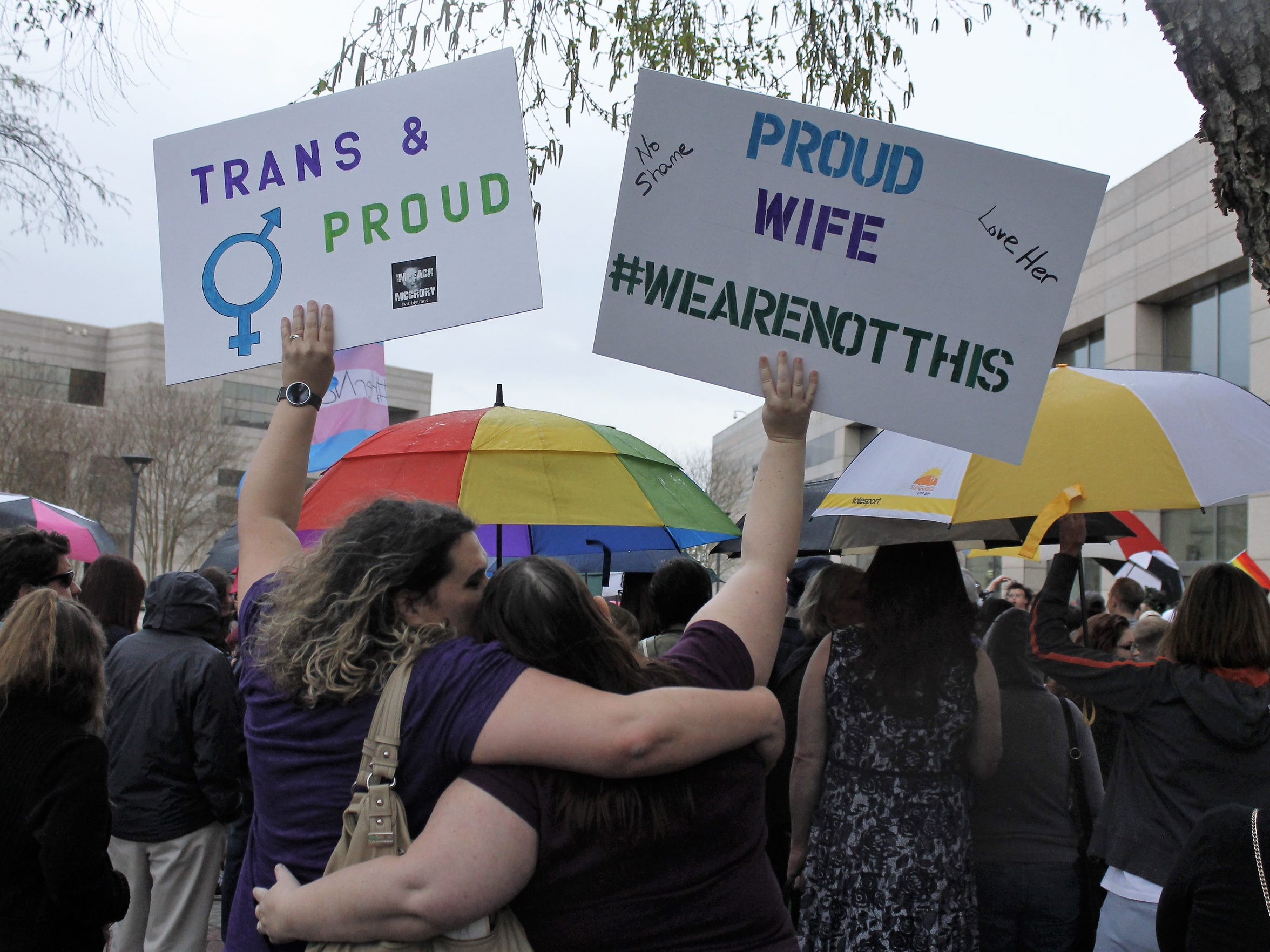Two protesters hold up signs against passage of legislation in North Carolina, which limits the bathroom options for transgender people, during a rally in Charlotte, N.C., Thursday, March 31, 2016.