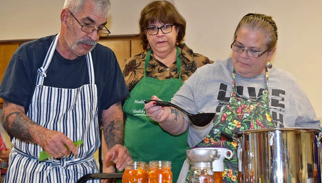 Cindy Davies, county director of NMSU Cooperative Extension Service in Bernalillo County, middle, watches Mark Genualdi and Karen Raistrick fill jars with vegetable soup while they pressure can the food for future use. Genualdi and Raistrick are among the first volunteers to enter the Bernalillo County Master Food Preservation program taught by Davies.
