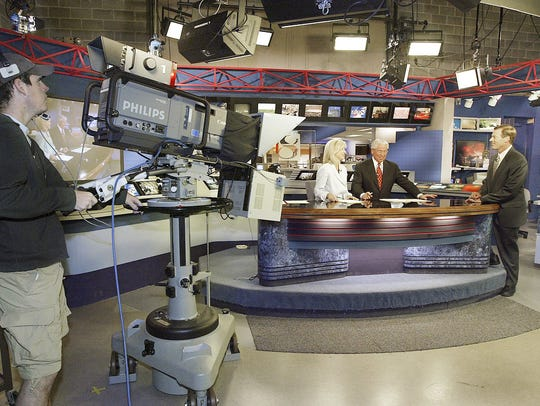 Barrett Tryon, left, an engineer at KCCI, operates