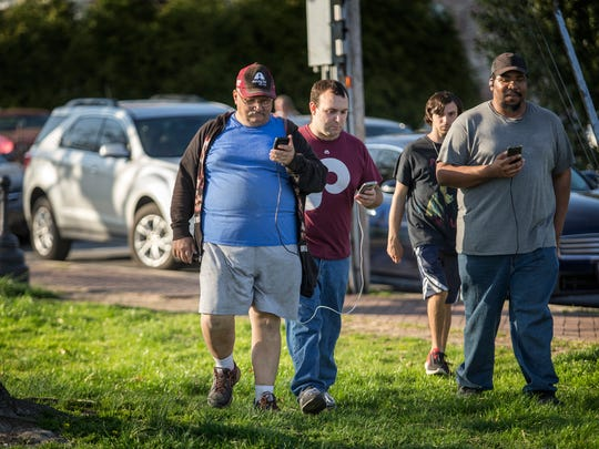 Pokemon Go players make their way through Battery Park as they look for virtual creatures in New Castle.