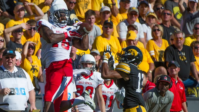 Sep 6, 2014; Iowa City, IA, USA; Ball State Cardinals wide receiver KeVonn Mabon (16) makes a catch over Iowa Hawkeyes defensive back Greg Mabin (13) at Kinnick Stadium. Iowa defeated Ball State 17-13.